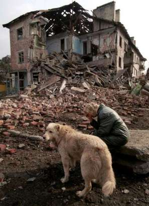 Woman and her Dog outside her bombed house, Grozny, Chechnya 1995. Photograph by Yuri Gripas