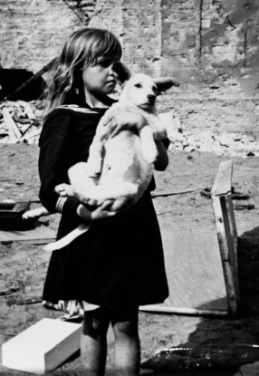 "'""A girl holding her dog in a devastated neighborhood in Warsaw, Poland, 5 Sep 1939"" by Julien Bryan'"