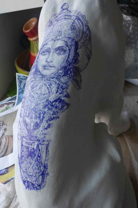 Detail of sculpture tattoo blue Biro drawing on curved back of tiger figurine
